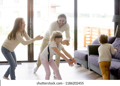 Happy funny family with little toddler son and daughter enjoy spending free time on weekend at new modern home. Playful small girl with covered eyes playing blindman game hide and seek in living room