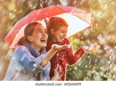 Happy funny family with red umbrella under the autumn shower. Girl and her mother are enjoying rainfall. Kid and mom are playing on the nature outdoors. Walk in the park.