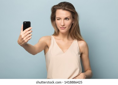 Happy funny flirty woman holding smartphone, making selfie shot, winking to camera, millennial blogger recording story or video for followers in social networks, posing on studio background.