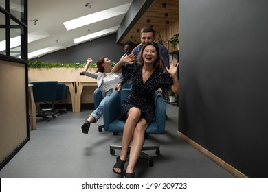 Happy funny friendly diverse coworkers having fun racing riding on chairs in modern office, asian employee laughing enjoying team building activity at work break laughing playing at workplace