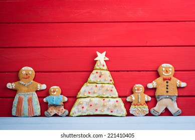 Happy funny gingerbread man family on wooden background with Christmas tree
