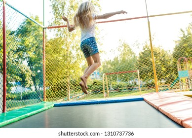 Happy funny girl jumping on trampoline. Back view
