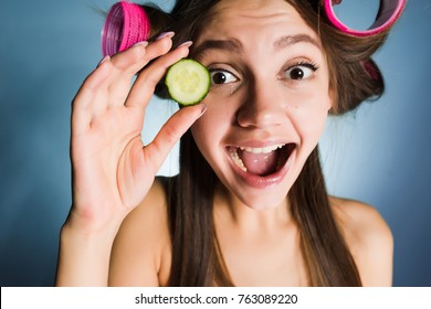 happy funny girl looks after her hair and face, on her hair curler's head to create a fashionable hairstyle, holds a piece of cucumber to moisten her face