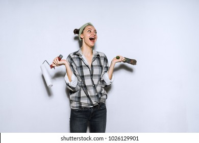 happy funny girl in a shirt doing repairs in her apartment, holding a roller and brush for painting the walls