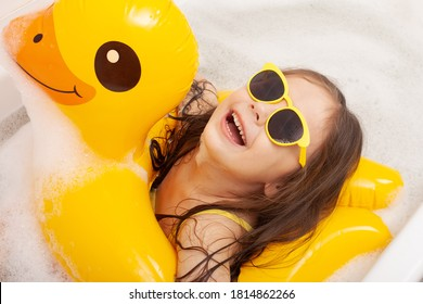 happy funny kid bathes in a bathtub with an inflatable duck