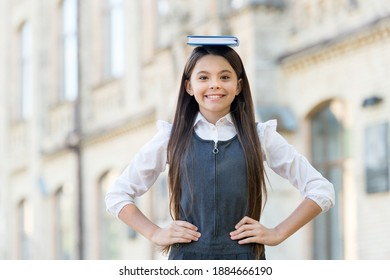 Happy funny kid with long hair in school uniform hold study book on head outdoors, bibliophile.