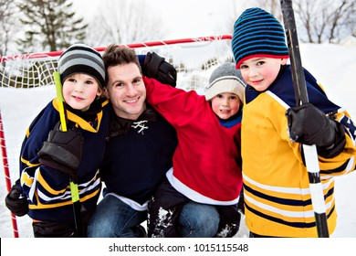 Happy funny kids playing hockey with father on street in the winter season