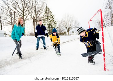 Happy funny kids playing hockey with father and mother on street in the winter season