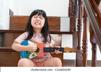 Happy funny little asian girl sing a song and playing ukulele at home.