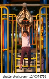 Happy funny little asian girl playing alone with monkey bar at the playground. Image of emotional cheerful adorable kid having fun in summer of outdoors. education activity for kid concept.