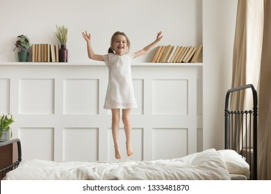 Happy funny little child girl in motion jumping on bed alone flying in air feeling joy, cheerful cute active kid having fun playing laughing in bedroom after waking up, good morning children concept