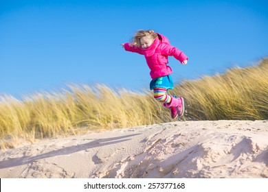 Happy funny little girl, adorable curly toddler, running and jumping in sand dunes enjoying family vacation at the North Sea, Holland, Netherlands on a sunny winter day at the beach