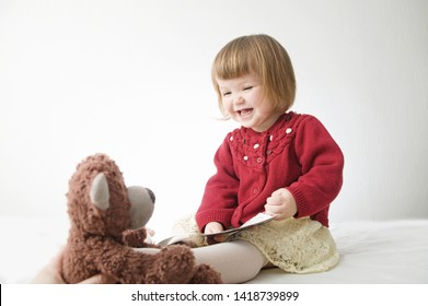 happy funny little girl emotional playing. cute caucasian blond baby girl with bear and doll