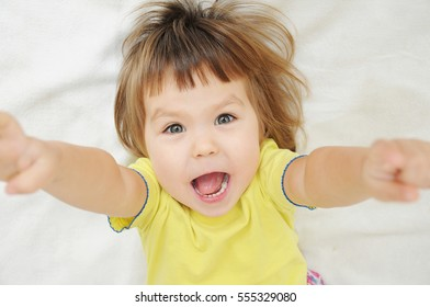 happy funny little girl with hands up lying on bed isolated, happy childhood concept