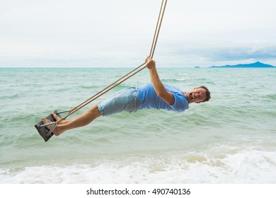 Happy and funny man on the beach swing.