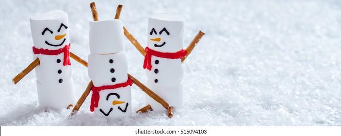 Happy funny marshmallow snowman are having fun in snow