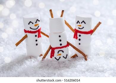 Happy funny marshmallow snowmen are having fun in snow