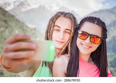 Happy and funny people make selfie or make pictures of themselves on mobile phone at mountain outdoor. They dressed at hipster style clothing, sunglasses, has long hair