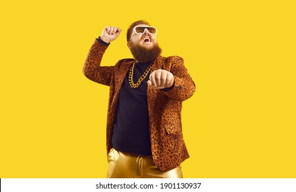 Happy funny plump young man singing songs and dancing gangnam style at a party. Funky redhead chubby guy having fun and doing rope dance move like cowboy with lasso isolated on amber color background