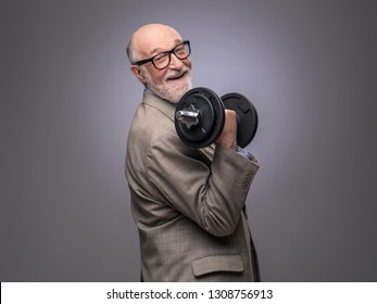 Happy funny senior man in suit with dumbbell, power concept