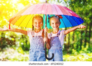 Happy funny  sisters twins  child by girl with a multicolored umbrella  laughing