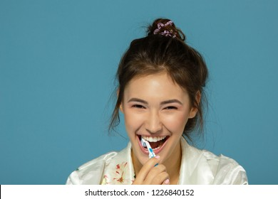 Happy funny teen girl brush her teeth, healthy concept. Morning theme, over blue background.