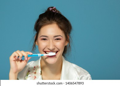 Happy funny teen girl brush her teeth, healthy concept, morning theme, isolated over blue background. Portrait of young beautiful woman during morning procedures