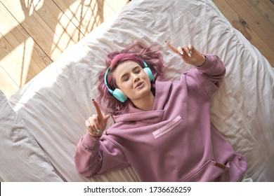 Happy funny teen girl with pink hair wear headphones lying in comfortable bed listening new pop music enjoying singing song with eyes closed relaxing in cozy bedroom at home. Top view from above.