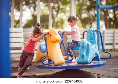 Happy funny two little children playing with merry go around at the playground. Image of emotional cheerful adorable asian kids having fun in summer of outdoors. education activity for kid concept.