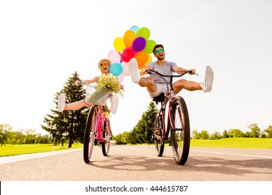 Happy funny young couple riding on bicycle with raised legs