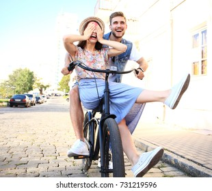Happy funny young couple riding on bicycle. Love, relationship, romance concept.