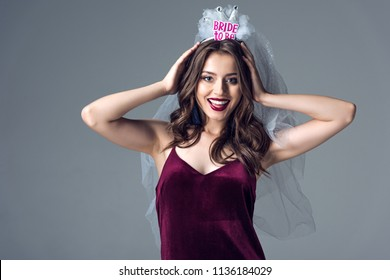 happy future bride in veil for bachelorette party looking at camera isolated on grey