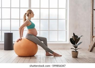 Happy future mother doing pilates exercises