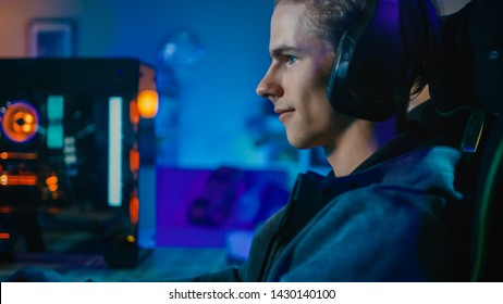 Happy Gamer and Blogger in Headset with a Mic Playing Shooter Online Video Game on His Personal Computer.  Room and PC have Colorful Neon Led Lights. Cozy Evening at Home.