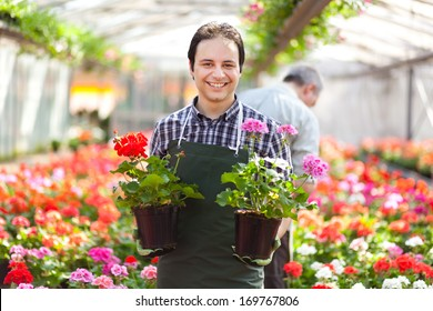 Happy gardener in a greenhouse holding flowers