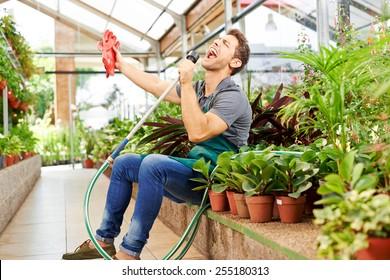 Happy gardener singing in water hose in a greenhouse of a nursery shop