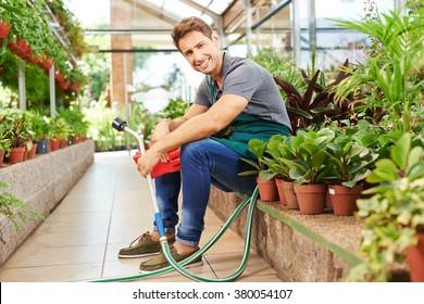 Happy gardener with water hose sitting between plants in a nursery shop