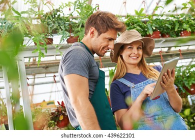 Happy gardener working with tablet computer in a greenhouse