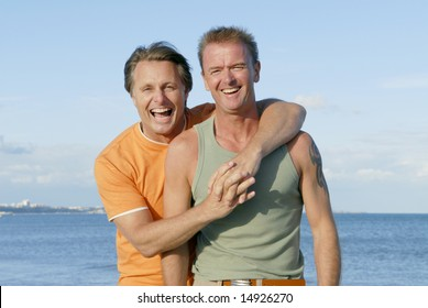 A happy gay couple enjoying a summer`s day on the beach together.