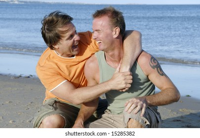 A happy gay couple having fun on the beach.