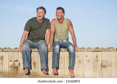 A happy gay couple are having fun together as they sit on the boardwalk at the beach.