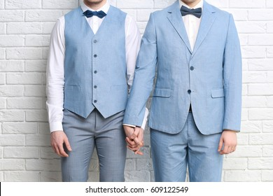 Happy gay couple holding hands together on brick wall background