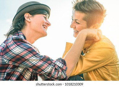 Happy gay couple looking at each other hand to hand - Young women lesbians having a tender moment outdoor - Lgbt, bisexuality, relationship lifestyle concept