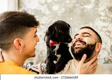 Happy gay couple in love looking at each other at home with their dog