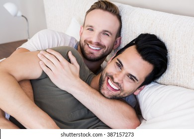 Happy gay couple lying on bed at home