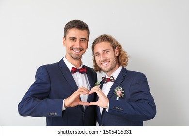 Happy gay couple making heart with their hands on wedding day against light background