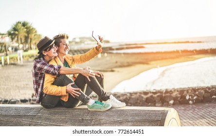 Happy gay couple taking selfie with smartphone next to the beach at sunset - Homosexuality relationship, lgbt and technology trends concept - Main focus on right girl face - Soft contrast filter