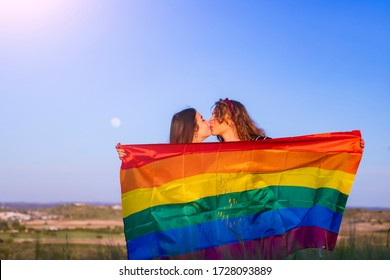 Happy gay girls couple kiss in front of gay flag