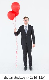 Happy geeky hipster businessman holding balloons on white background