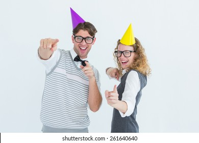 Happy geeky hipster couple dancing with party hat on white background